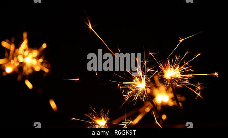 Close up several firework sparklers over black - Stock Photo