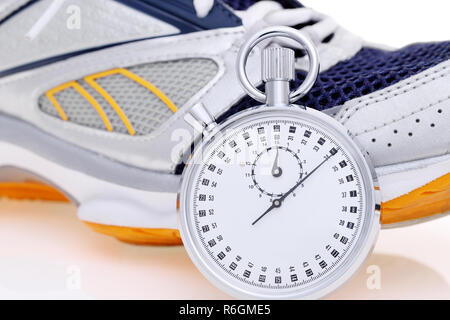 analogue stopwatch with sport running shoes on white background - Stock Photo
