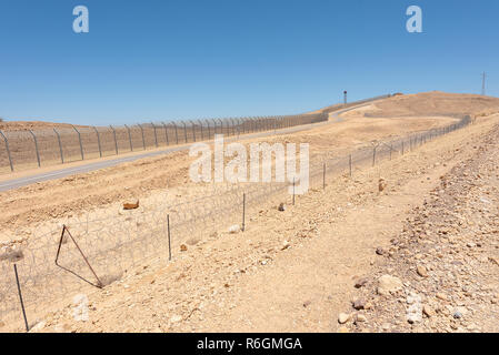 Israel Egypt border fence in the Negev and Sinai deserts - Stock Photo