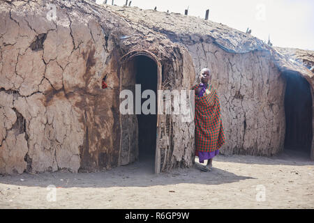 A young lady Masai in front of the Masai House - Stock Photo