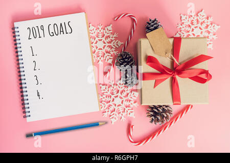 2019 Goals, top view brown gift box, notebook and christmas decoration for new year on pink pastel color. - Stock Photo