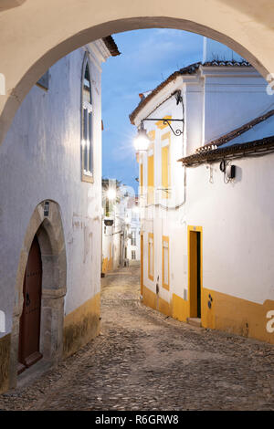 Cobbled narrow street in the old town with whitewashed houses at dawn, Evora, Alentejo, Portugal, Europe - Stock Photo