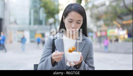 Woman eating fish ball, Hong Kong style snack - Stock Photo