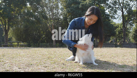 Woman playing with her dog at outdoor park - Stock Photo