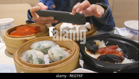 Woman taking photo with cellphone on chinese dim sum - Stock Photo