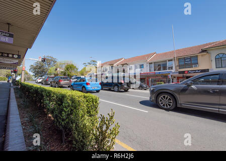 Looking south, shops line the Pacific Highway at Gordon on Sydney Australia's north shore as traffic waits at a red light on a Saturday morning. - Stock Photo