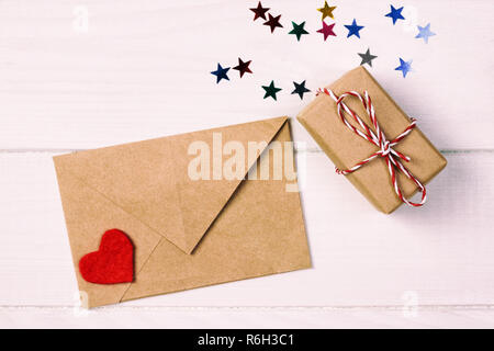 Envelope Mail with Red Heart and gift box over White toned, vintage Wooden Background. Valentine Day Card, Love or Wedding Greeting Concept. - Stock Photo