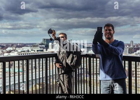London/UK - March 25 2018: two men taking selfies against London cityscape - Stock Photo