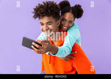 Photo of beautiful african american woman taking selfie while hugging brother from back isolated over violet background - Stock Photo