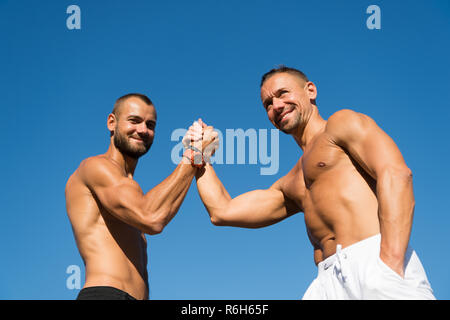 Happy and confident. Muscular men do arm wrestling sport. Happy men enjoy good health. Health care. Success in sport. Developing muscular strength and power. The key to success is action. - Stock Photo