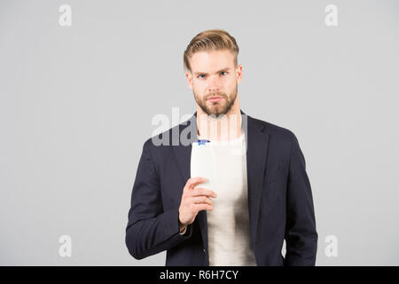 Dandruff common male problem. Remedies get rid of dandruff. Man formal suit hold bottle shampoo grey background. Itchy scalp and flakiness skin. Shampoo solve dandruff problem. Anti dandruff shampoo. - Stock Photo