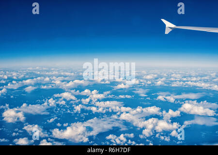 aerial view on sunny blue cloudy sky with white clouds from plane with wing as natural background, travel, wanderlust - Stock Photo