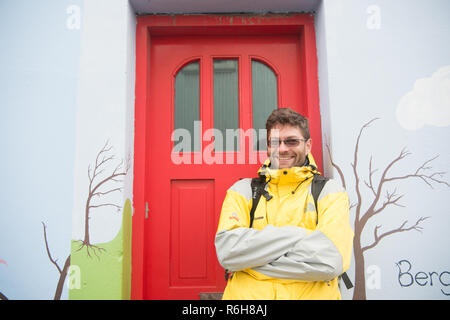 Reykjavik, Iceland - October 12, 2017: happy man tourist. Active man stand at house door. Tourist agency. As happy as a clam. Travel more get happy, - Stock Photo