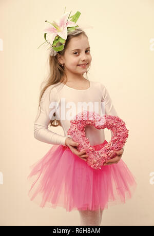 small baby girl dancer, cute child ballerina with happy face and lily flower in blonde hair in bodysuit and pink tutu skirt holding valentines day holiday decorative heart isolated on white background - Stock Photo