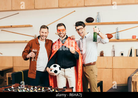 portrait of smiling man in superhero costume with soccer ball in hand and friends near by in cafe - Stock Photo