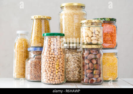 Various uncooked cereals, grains, beans and pasta for healthy cooking in glass jars - Stock Photo