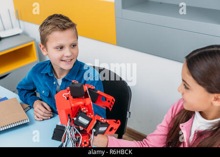 smiling schoolchildren sitting at desk and looking at each other in stem class - Stock Photo