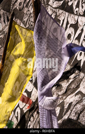 Nepal, Benkar, prayer flags at huge painted, carved Buddhist mani stone on Everest Base Camp Trek path - Stock Photo