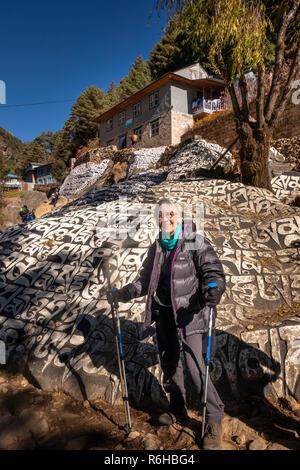Nepal, Benkar, senior trekker at huge painted, carved Buddhist mani stone on Everest Base Camp Trek path - Stock Photo