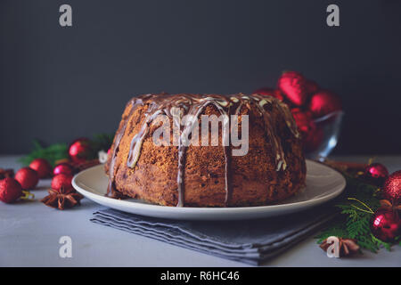 Christmas cake with chocolate icing on gray wooden background. Holiday decorations concept. Top view. Flat lay. Copy space. Toned - Stock Photo