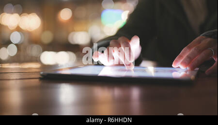 Using tablet computer at outdoor coffee shop - Stock Photo