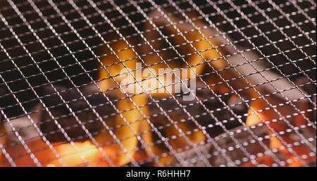Charcoal fire with metal net - Stock Photo