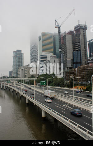 View of a bridge in downtown Brisband with fog and blurred cars in the morning. - Stock Photo