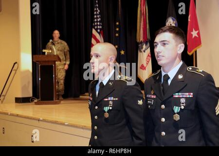 Spc. James Harris, a Stryker Gunner with B Troop, 5-1 Cavalry, 1st Stryker Brigade Combat Team and Sgt. Brett Nicholls, a team leader from the same troop as Harris, sing the U.S. Army Alaska March after being named the USARAK Best Warriors for 2017. Eight candidates from units all over Alaska participated in the five-day competition to determine who represents USARAK at the U.S. Army Pacific Soldier and NCO of the Year Board in June. - Stock Photo