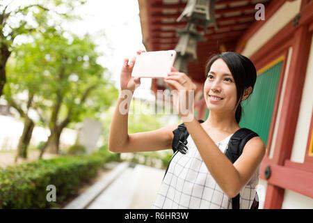 Traveler taking photo in Dazaifu Tenmangu Shrine - Stock Photo