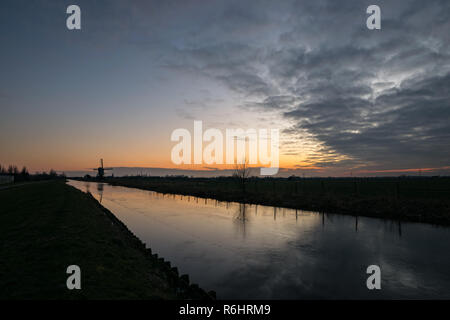 A dutch canal is covered with ice. A distant windmill is silhouetted against the evening sky. Scenic view of the dutch landscape in winter. - Stock Photo