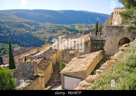 Rooftops of old houses in Luberon, southern France region. warm colors and green hills shot from a elevated point of view. - Stock Photo