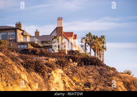 Sunset view of mansions built on top of cliffs on the Pacific Ocean coast, Malibu, Los Angeles county, California - Stock Photo