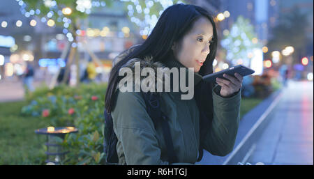 Woman sending audio message on cellphone at night - Stock Photo