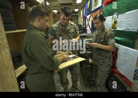 Sergeant Kyle J. Gorman, a satellite communications technician assigned to Special Purpose Marine Air-Ground Task Force-Crisis Response-Africa, delivers hand written letters to Cpls. James D. Hussey III, a communications repair technician and Ivett Romerobenitez, an assistant wire chief with SPMAGTF-CR-AF, at Morón Air Base, Spain, May 19, 2017. The letters were written by third grade students from Freedom Elementary School in Brandenton, Fla. - Stock Photo