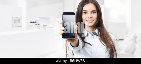 smart home control concept smiling woman showing cell phone screen on kitchen and living blurred background - Stock Photo