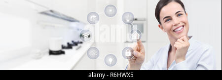 smart home automation smiling woman hand touch screen with white symbols on kitchen background web banner and copy space template - Stock Photo