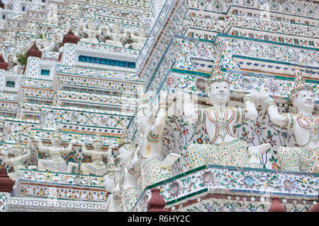 White Yaksha and dancer statues in Wat Arun temple in Bangkok, Thailand. The demon-gods statues are a common sight in Buddhist temples in Thailand, bu - Stock Photo