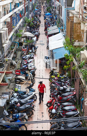 High angle shot of narrow street with several mopeds parked amongst residential buildings and pedestrian walking past. In Bangkok, Thailand. - Stock Photo