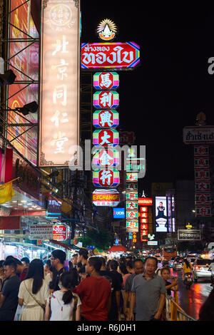 Night shot of busy Chinatown district in Bangkok, Thailand, with lots of pedestrians and neon signs. - Stock Photo