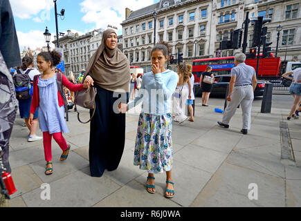 Muslim woman with her two daughters, London, England, UK. - Stock Photo
