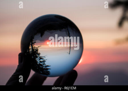 Sunset over California's Sierra Nevada mountains with sun and ridges on horizon and trees in silhouette.  Captured in glass globe reflection. - Stock Photo