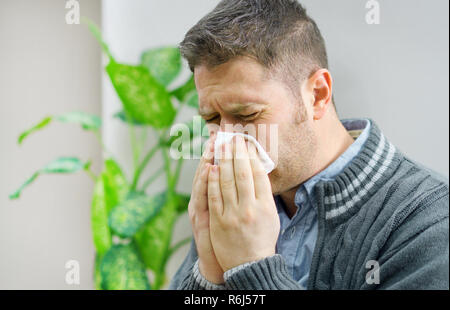 Handsome unshaved man blowing nose to napkin. - Stock Photo