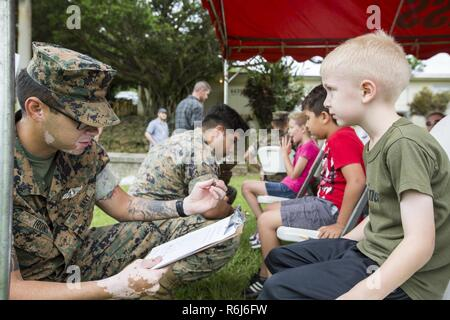 U.S. Navy Petty Officer 3rd Class Joseph Irons, a Hospital Corpsman with Headquarters Battalion, 3rd Marine Division, conducts a check up on a Marine Corps service member's son aboard Camp Courtney, Okinawa, Japan, May 20, 2017. 3rd Marine Division hosted a Kids Warrior Day to help bring the families of Marines and Sailors closer together and give them the opportunity to see what their Marine or Sailor is doing throughout the Division. - Stock Photo