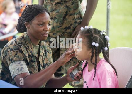 U.S. Marine Corps Cpl. Molly Karani, a motor transportation mechanic with Truck Co, Headquarters Battalion, 3rd Marine Division, paints the face of a Marine Corps service member's daughter aboard Camp Courtney, Okinawa, Japan, May 20, 2017. 3rd Marine Division hosted a Kids Warrior Day to help bring the families of Marines and Sailors closer together and give them the opportunity to see what their Marine or Sailor is doing throughout the Division. - Stock Photo