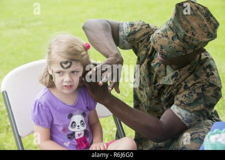 U.S. Marine Corps Lance Cpl. Andre Smith, a field wireman with Communications Co, Headquarters Battalion, 3rd Marine Division, helps paint face on Camp Courtney, Okinawa, Japan, May 20, 2017. 3rd Marine Division hosted a Kids Warrior Day to help bring the families of Marines and Sailors closer together and give them the opportunity to see what their Marine or Sailor is doing throughout the Division. - Stock Photo