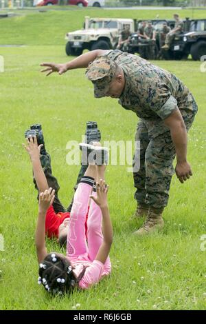 U.S. Marine Corps Cpl. Brian Diaz, a motor transportation mechanic with Truck Co, Headquarters Battalion, 3rd Marine Division, simulates a drill instructor to motivate the children of Marines and Sailors of 3rd Marine Division aboard Camp Courtney, Okinawa, Japan, May 20, 2017. 3rd Marine Division hosted a Kids Warrior Day to help bring the families of Marines and Sailors closer together and give them the opportunity to see what their Marine or Sailor is doing throughout the Division. - Stock Photo