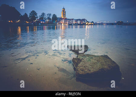 Deventer at night with view over the river Ijssel from a beach. The tower church is towered above the beautifully-featured cityscape. - Stock Photo