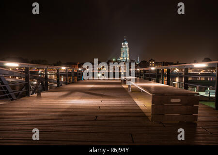 Deventer at night with view from a jetty over the river Ijssel. The tower of the Lebuinus church is towered above the beautifully lit cityscape. - Stock Photo