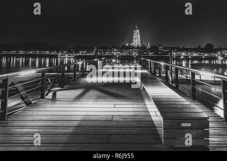 Deventer at night with view from a jetty over the river Ijssel. The tower of the Lebuinus church is towered above the beautifully lit cityscape.  Blac - Stock Photo