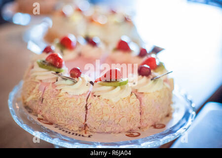 Beautifully decorated catering banquet table with different cakes as cottage cheese, apple and whipped cream on birthday party - Stock Photo